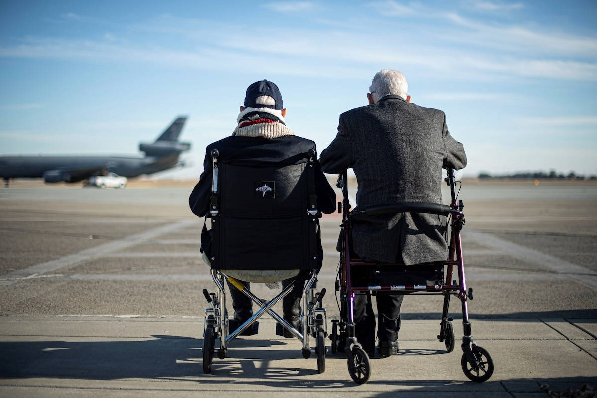 Two veterans sit in chairs on a flightline and watch an aircraft taxi.
