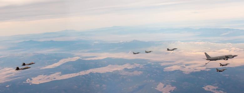 F-22s, F-15Es and F-16s fly alongside a KC-46