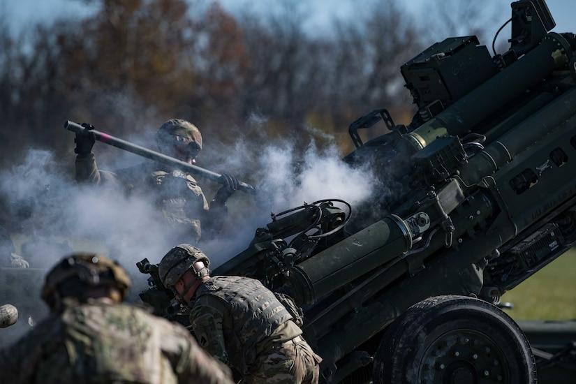 Soldiers reload an artillery piece after firing.