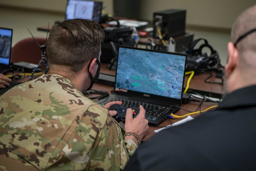 A service member looks at a laptop screen.