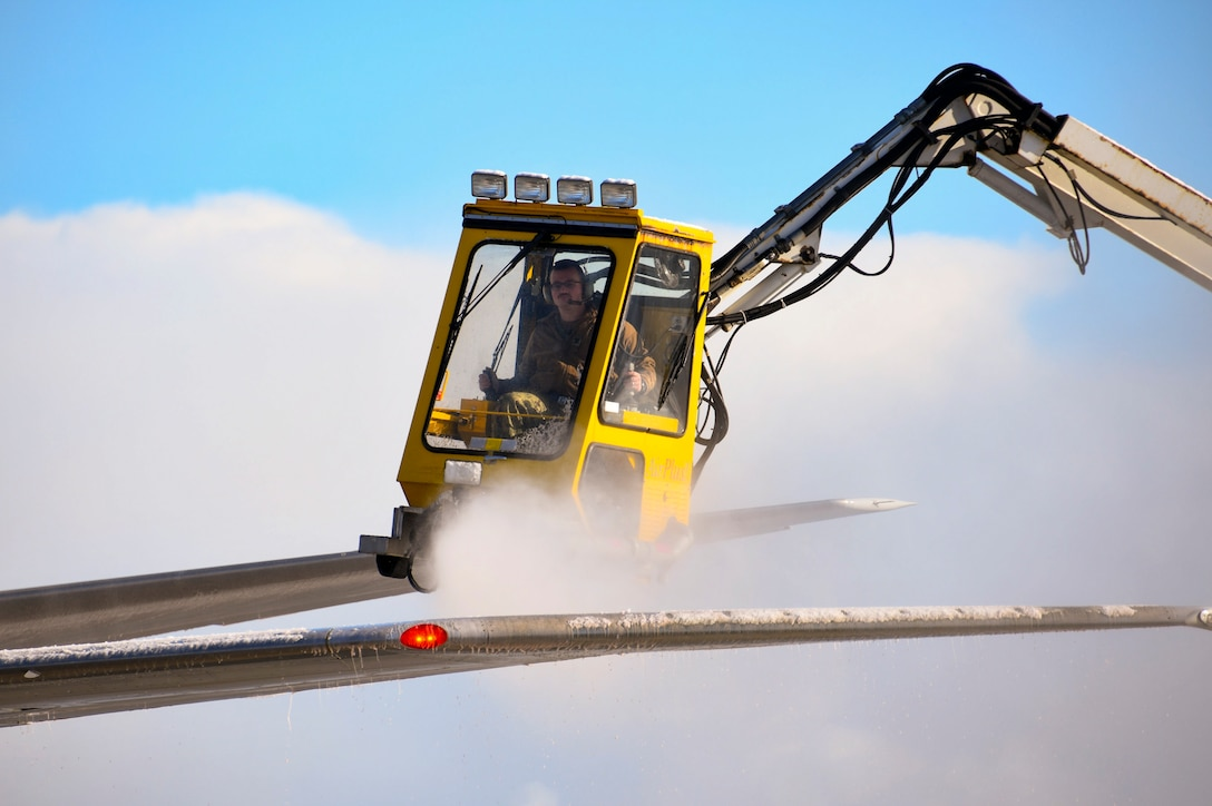 A sailor operates a de-icing truck to remove snow and ice from an aircraft's wing.