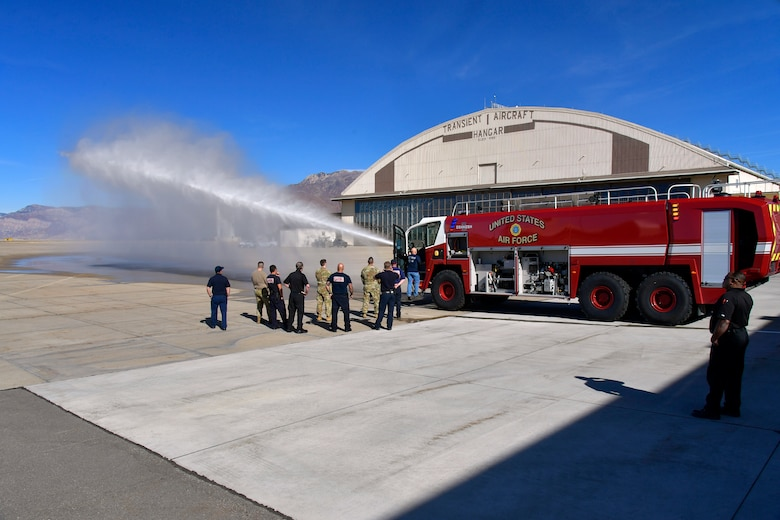 Firefighters watch as the water cannon attached to a newly delivered crash/fire response vehicle sprays water.