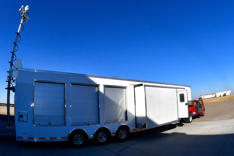 The MEOC trailer hooked to the back of a red pick up truck.