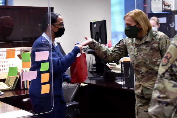 U.S. Air Force Chief Master Sgt. Casy Boomershine, 17th Training Wing command chief, gives a Goodfellow member a goody bag in the Norma Brown Building on Goodfellow Air Force Base, Texas, Nov. 17, 2020. Col. Andres Nazario, 17th Training Wing commander and Boomershine handed bags out to several offices in multiple squadrons. (U.S. Air Force Photo by Staff Sgt. Seraiah Wolf)