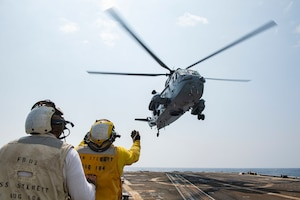 Damage Controlman 1st Class Ryan Sandoval, from Redlands, Calif., monitors Boatswain's Mate 2nd Class Kelvin Tyler, from Philadelphia, as he directs an Indian Navy Sea King Mk42B helicopter during a Malabar 2020 cross deck landing exercise on the flight deck of the guided-missile destroyer USS Sterett (DDG 104).