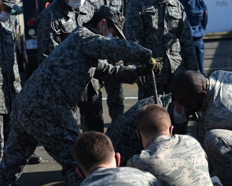 Individuals in uniform perform training outside