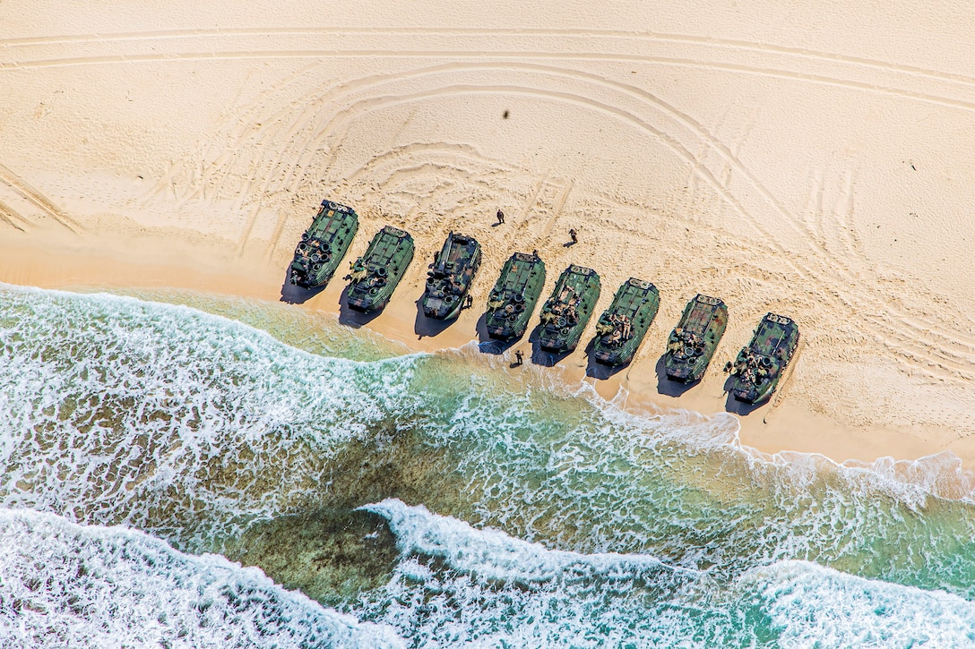 Eight vehicles in a row on a  beach are seen from above.
