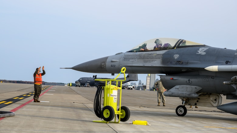 A U.S. Airman with the 35th Air Maintenance Squadron directs an F-16 Fighting Falcon during a forward area refueling point training (FARP) exercise at Misawa Air Base, Japan, Nov. 18, 2020. FARP is the rapid transfer of fuel from one aircraft to another. This capability makes it possible for fighter aircraft to land, replenish fuel and return to air-battle operations within a short timeframe in austere environments. (U.S. Air Force photo by Airman 1st Class China M. Shock)