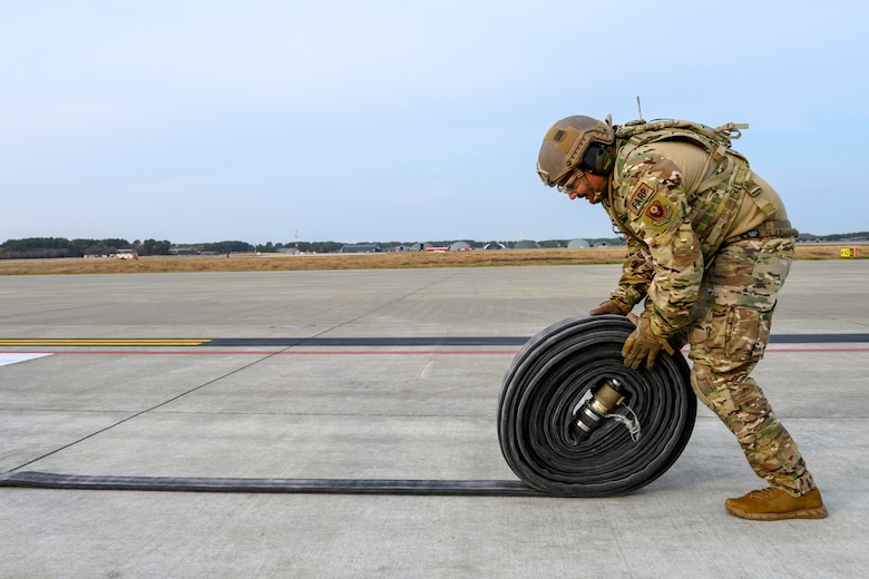 A U.S. Airman with the 1st Special Operations Squadron from Kadena Air Base, Japan, rolls up a fuel hose during a forward area refueling point (FARP) training at Misawa Air Base, Japan, Nov. 18, 2020. FARP ensures the rapid transfer of fuel from one aircraft to another. In this case, an MC-130J and two F-16 Fighting Falcons. (U.S. Air Force photo by Airman 1st Class China M. Shock)