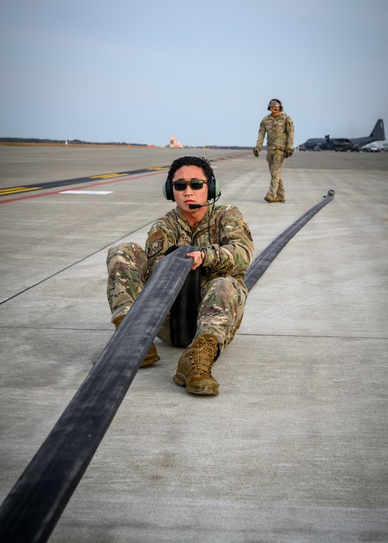 A U.S. Airman with the 1st Special Operations Squadron from Kadena Air Base, Japan, holds a fuel hose steady during a forward area refueling point (FARP) training at Misawa Air Base, Japan, Nov. 18, 2020. With FARP support, any accessible airfield or island can be used to replenish aircraft and get them back to the fight, delivering airpower lethality. (U.S. Air Force photo by Airman 1st Class China M. Shock)