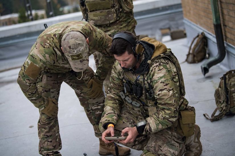 A service member crouches on the ground to look at an instrument in his hand as another service member leans down to observe.