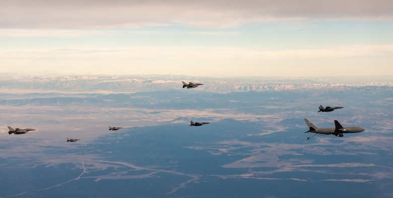 F-15Es and F-16s fly alongside a KC-46