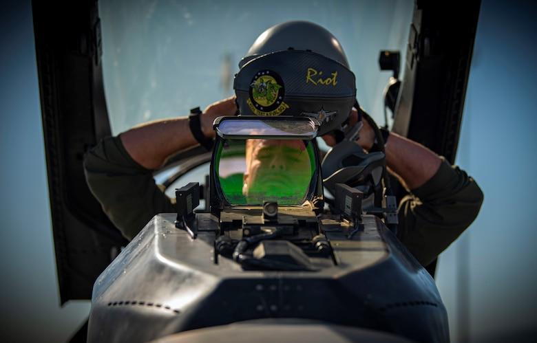 a pilot puts on his helmet
