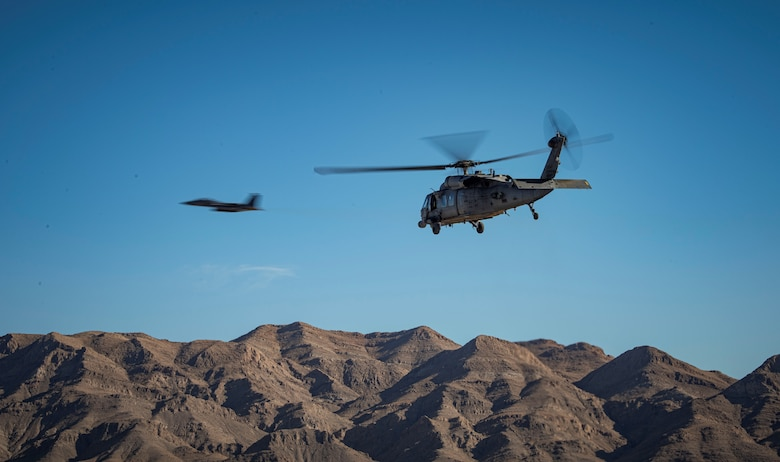 A helicopter flies over mountains with a jet in the background