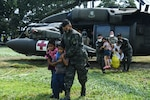 Joint Task Force-Bravo members and Honduran soldiers escort rescued Honduran family off of U.S. Army HH-60 Black Hawk helicopter at San Pedro Sula, Honduras, Nov. 13, 2020. JTF-Bravo's forward deployment to Honduras highlights the importance of cooperation and training with partners to build trust and teamwork. (U.S. Air Force photo by Staff Sgt. Elijaih Tiggs)