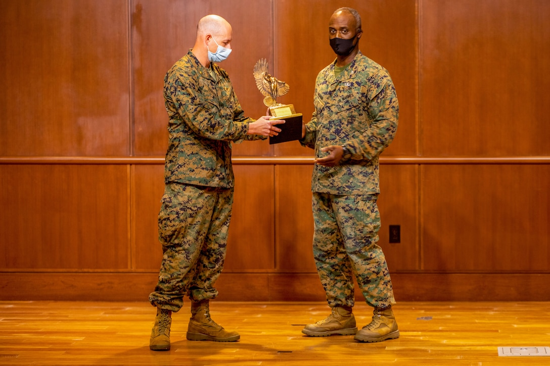 Col. Gerald Graham, the 4th Marine Aircraft Wing chief of staff, passes the Admiral James S. Russell Naval Aviation Flight Safety Award to Maj. Jonathan Hansen, 4th Marine Aircraft Wing director of safety and standardization, during an award ceremony on Nov. 13, 2020 at Marine Corps Support Facility New Orleans. Pilots with 4th MAW flew more than 20,000 hours with no Class A flight-related or aviation-ground mishaps, which placed it at the top of other competitive commands. (U.S. Marine Corps photo by Lance Cpl. Mitchell Collyer)