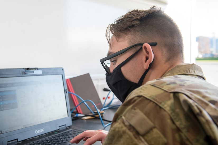 An airman wearing a face mask works on a laptop.