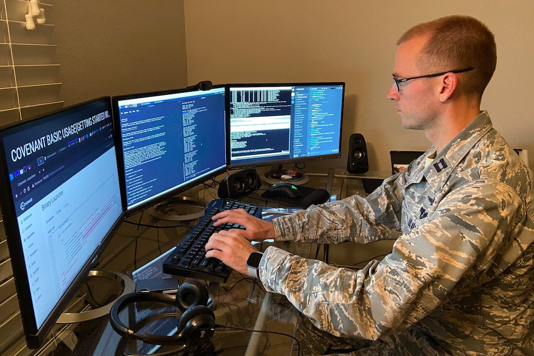 A man in a military uniform types on a keyboard and looks at three monitors.
