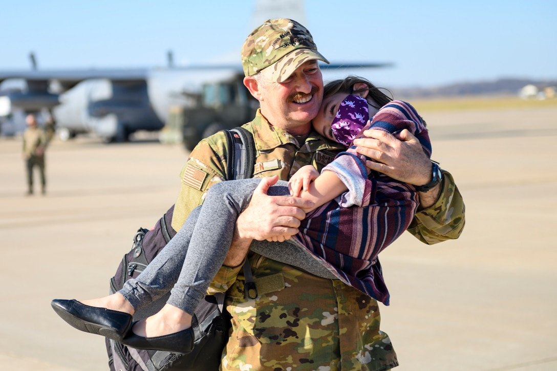 A smiling airman holds a smiling child on a flightline