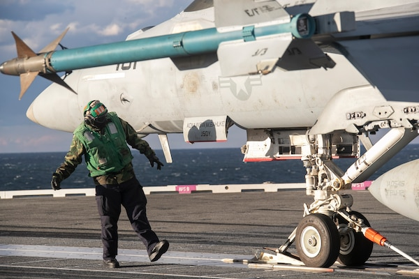 "A Sailor conducts a safety check on an F/A-18F Super Hornet attached to the ""Jolly Rogers"" of Strike Fighter Squadron (VFA) 103 during cyclic flight operations, Nov. 17, 2020."