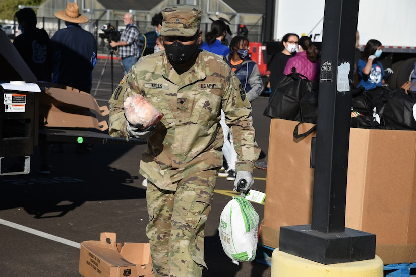 A soldier wearing a face mask carries two frozen turkeys across a parking lot.