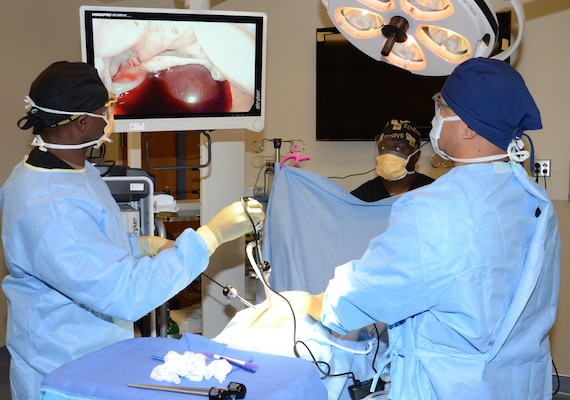 (Front, left to right) Petty Officer 1st Class Wesley Middleton and Petty Officer 2nd Class Domenick Llanda, instructors in the Medical Education and Training Campus Surgical Technologist program, conduct a mock laparoscopic procedure while Petty Officer 1st Class Forest Stewart (center), also an instructor, assists the team. Army, Navy and Air Force ST students are becoming familiar with laparoscopic and laparotomy procedures, which are more universally practiced in the surgical field, after curriculum update to move the training forward.