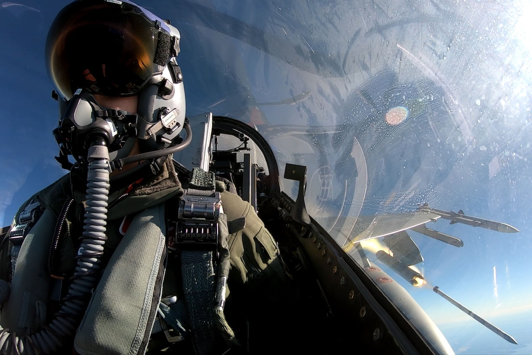 A military pilot wearing an oxygen mask sits in an aircraft cockpit while firing a rocket from his plane.