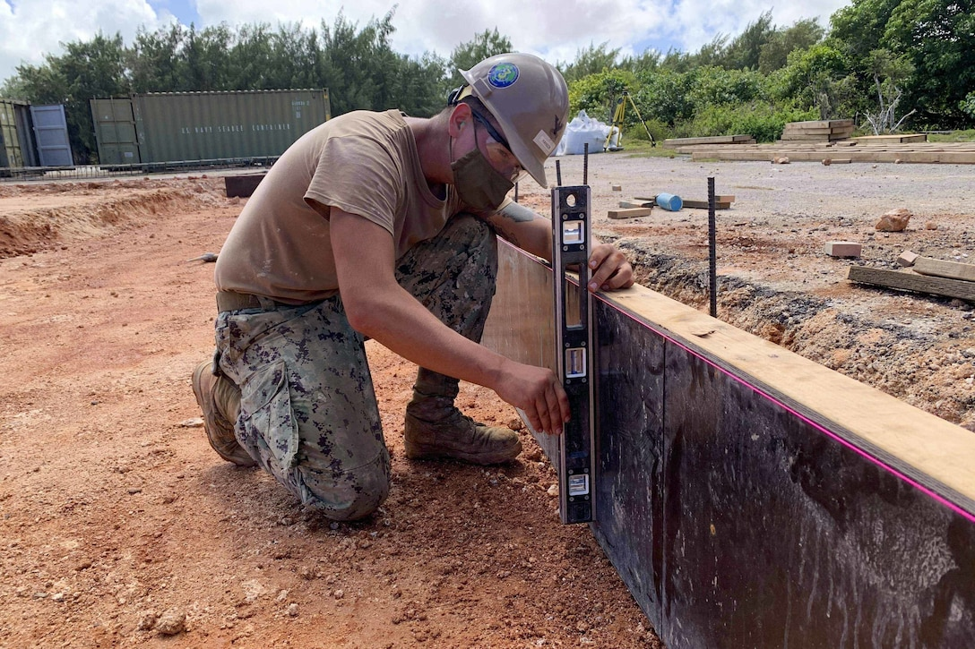 A sailor kneels in the dirt while using a tool to take a measurement  of a low wall.