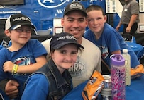 Staff Sgt. Jeffrey White, 7th Space Operations Squadron space system operator, and his children pose for a photo at Bandimere Speedway in Morrison, Colorado, June 2015. Through the Combined Federal Campaign, White was able to access the Make-A-Wish Foundation, because it was one of the organizations within the campaign. White's family traveled to Walt Disney World in Orlando, Florida, where his daughter's wish was granted by allowing her to spend time with her favorite Disney princess, Princess Jasmine. (U.S. Space Force courtesy photo)