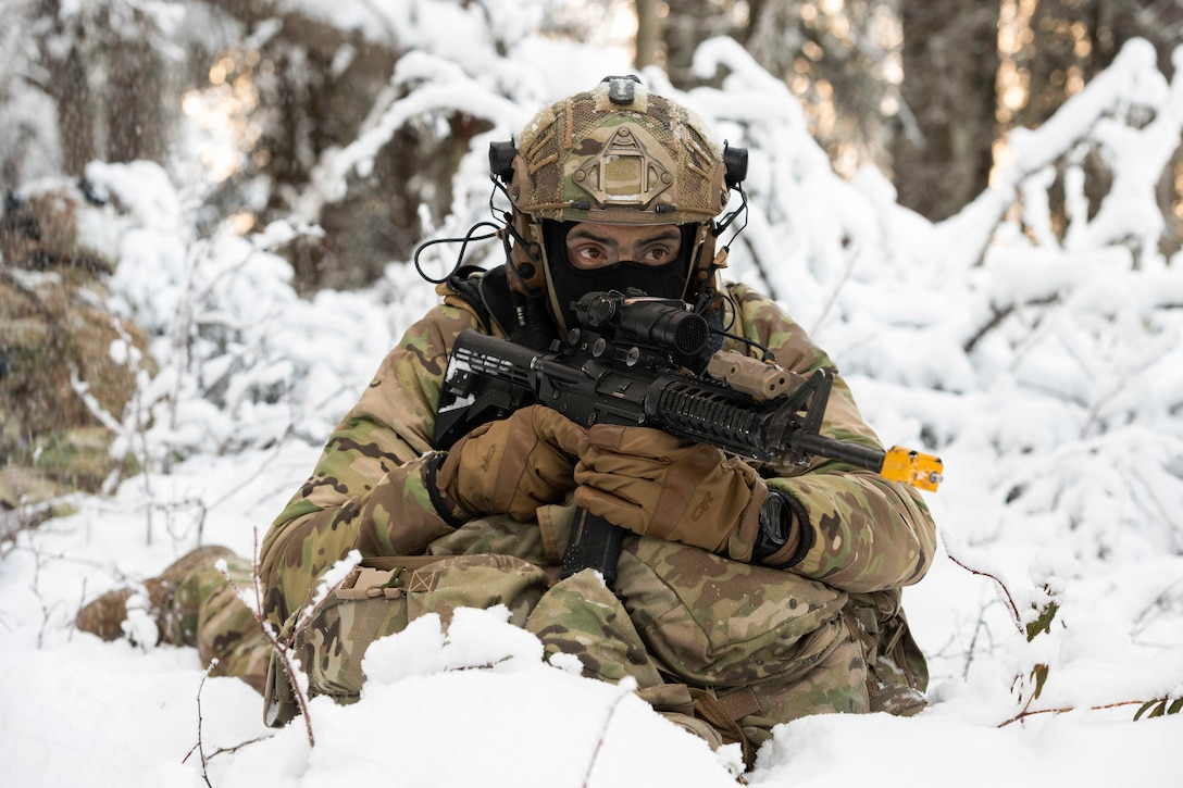 An airman holds a weapon while sitting in snow.
