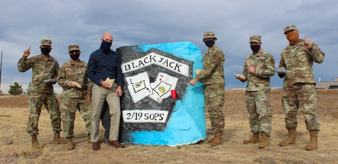 Members of the 19th Space Operations Squadron gather around the spirit rock displaying namesakes outside the fitness center to celebrate their cornhole championship Nov. 18, 2020, at Schriever Air Force Base, Colorado. The 19th SOPS won the base's first-ever intramural cornhole tournament and beat 22nd SOPS 21-16, 21-19 in the finals. The ongoing pandemic scrapped other intramural sports and caused the 50th Force Support Squadron to create fun, alternative sports. (U.S. Space Force photo by Marcus Hill)