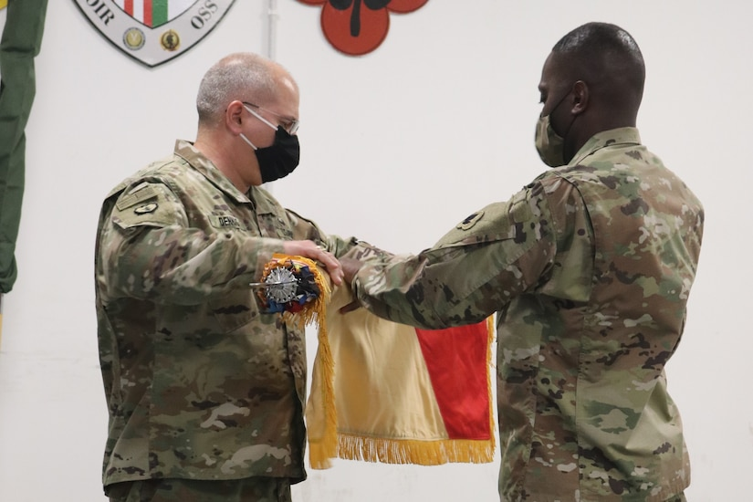 Col. Thomas Dennis and Command Sgt. Maj. Jimmie Smith uncase the 143rd Regional Support Group colors after the transfer of authority ceremony for Area Support Group-Jordan. The 143rd RSG mobilized to Jordan this month to provide support operations for U.S. forces in Jordan. The U.S. military is in Jordan to partner with the Jordan Armed Forces to meet common security objectives in the region.