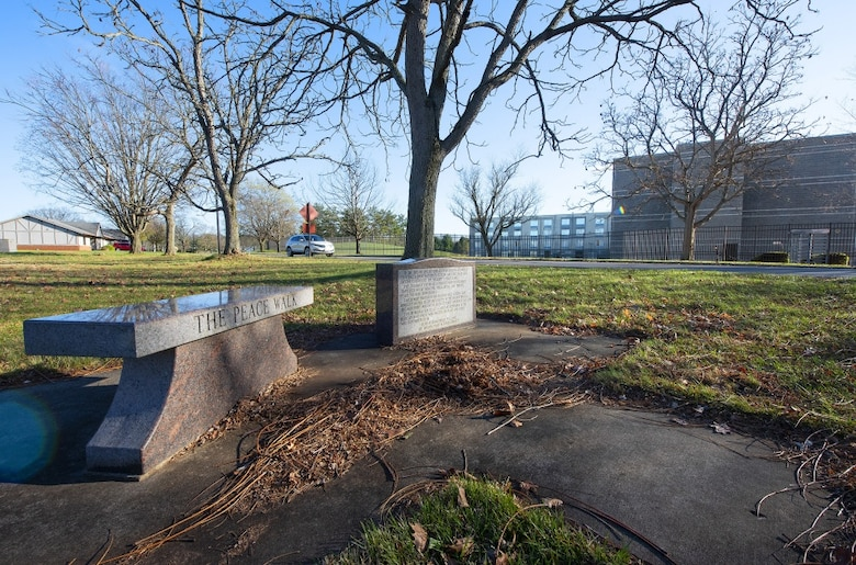 A bench and plaque commemorate the Peace Walk, a winding sidewalk between the Hope Hotel (background), which served as site of the official negotiations leading to the Dayton Peace Accords, and visiting officer quarters on Wright-Patterson Air Force Base, where the diplomats stayed. The unofficial talks that happened as the diplomats walked back and forth are credited with playing a role in the successful end of the Bosnian War. (U.S. Air Force photo by R.J. Oriez)
