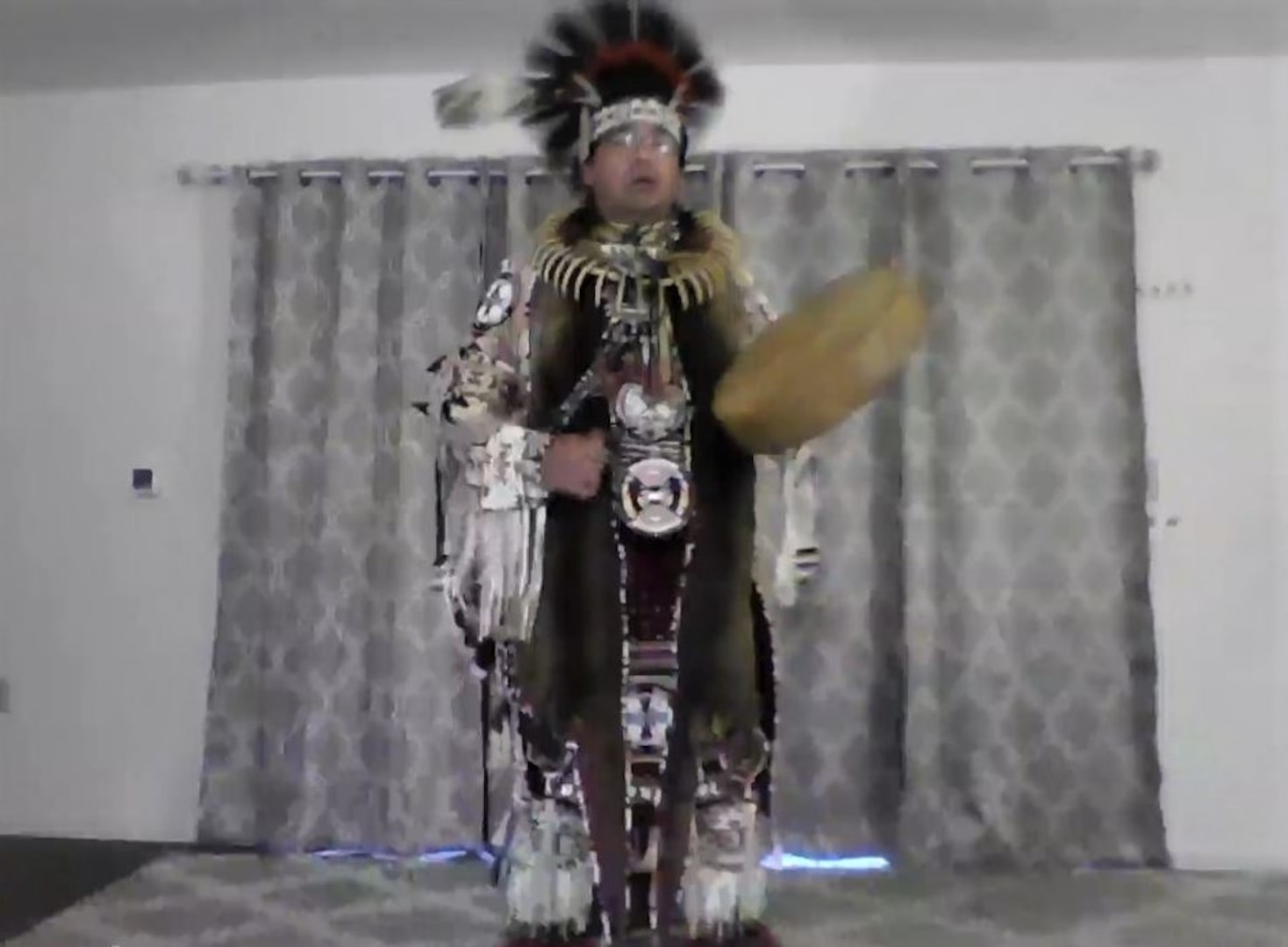 A Native American man wearing traditional garb performs a dance.