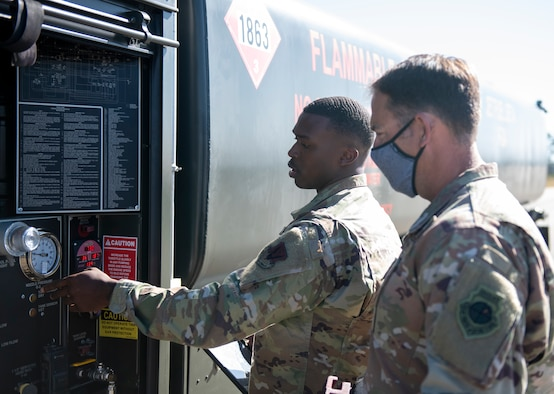 U.S. Air Force Senior Airman shows U.S. Air Force Colonel gauges on the side of a R-11 fuel truck.