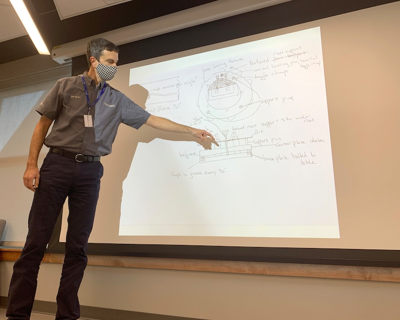 Tyler Rourke with Electroimpact, out of Washington state, showcases a sketch of his prototype to solve drilling B-52 brakes during a Design Sprint held at STRIKEWERX in Bossier City, La., Nov. 16-19, 2020.