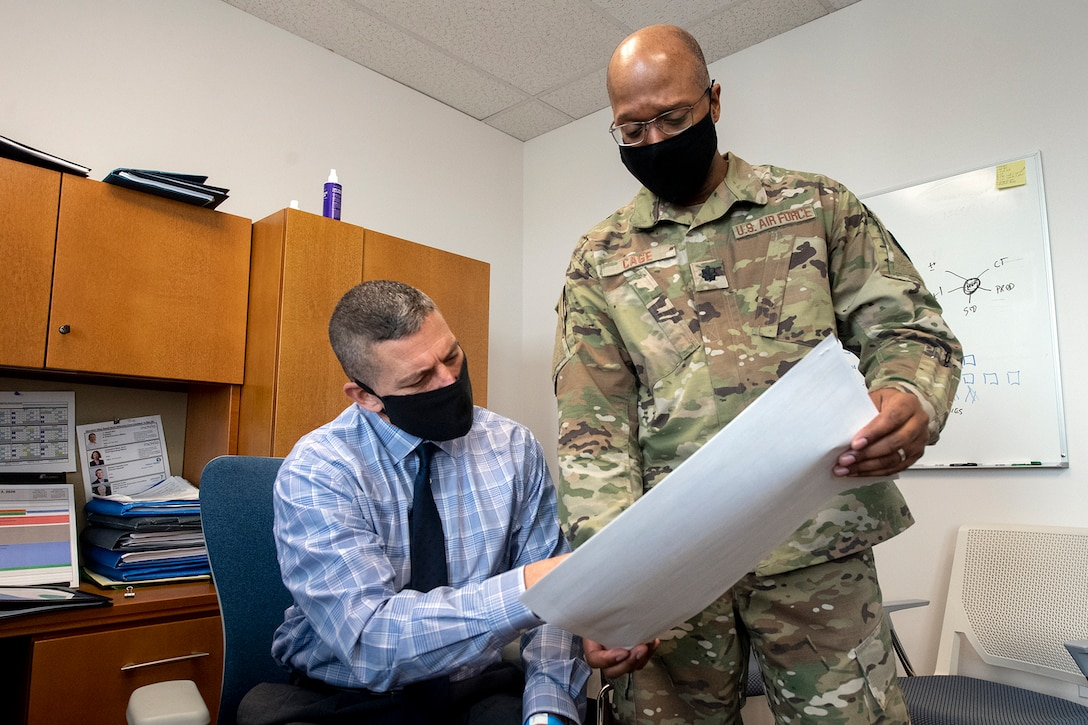 Two men review paperwork in an office.