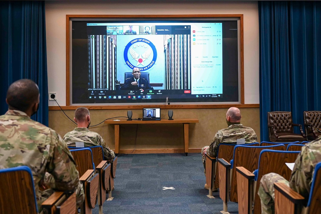 Airmen sitting in an auditorium listening to a virtual speaker