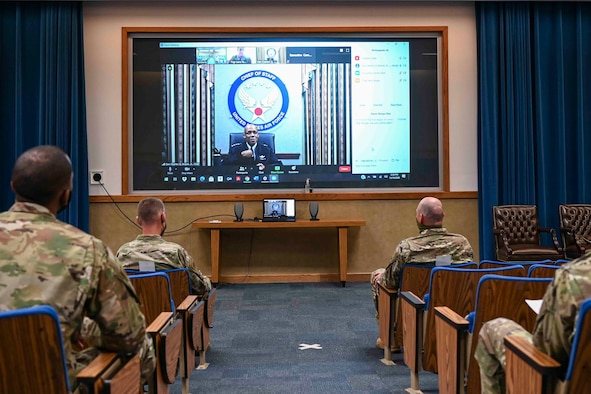 Airmen sitting in an auditorium listening to a virtual speaker