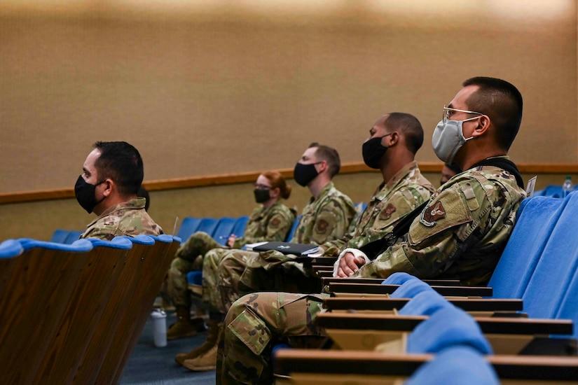 Airmen sitting in an auditorium listen to a speaker.