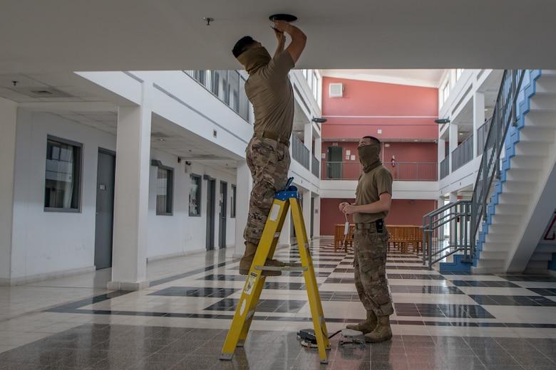 Airmen install light fixture