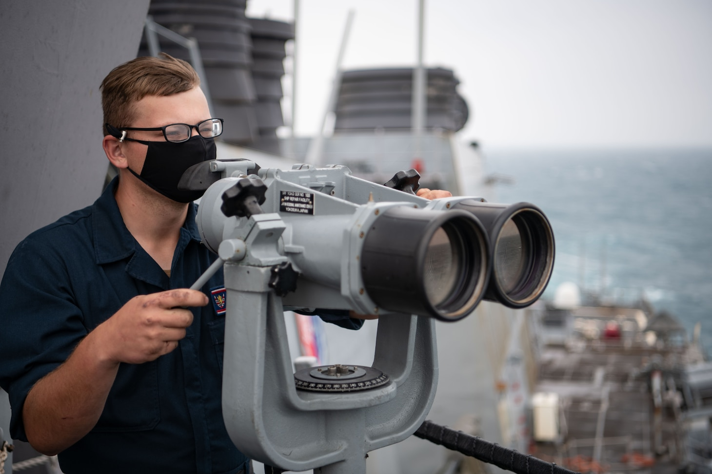 TAIWAN STRAIT (Nov. 20, 2020) – Boatswain's Mate Seaman Evan Sand, from Clearwater, Minn., uses the ship's binoculars to search for contacts on the bridge-wing of the guided-missile destroyer USS Barry (DDG 62) as the ship conducts routine underway operations in the Taiwan Strait. Barry is assigned to Destroyer Squadron (DESRON) 15, the Navy's largest forward-deployed DESRON and the U.S. 7th Fleet's principal surface force, forward-deployed to the U.S. 7th Fleet area of operations in support of a free and open Indo-Pacific. (U.S. Navy photo by Lieutenant Junior Grade Samuel Hardgrove)