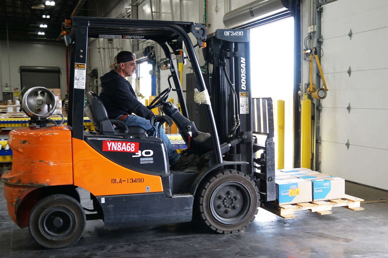 A man in a forklift transports supplies.