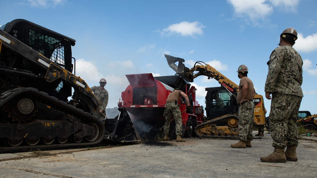 U.S. Air Force 18th Civil Engineer Squadron Airmen and Navy Mobile Construction Battalion 3 Seabees recycle asphalt during a rapid airfield damage repair exercise Nov. 18, 2020, at Kadena Air Base, Japan. The joint training enabled the two units to synchronize training, tactics and procedures for RADR operations. (U.S. Air Force photo by Staff Sgt. Peter Reft)