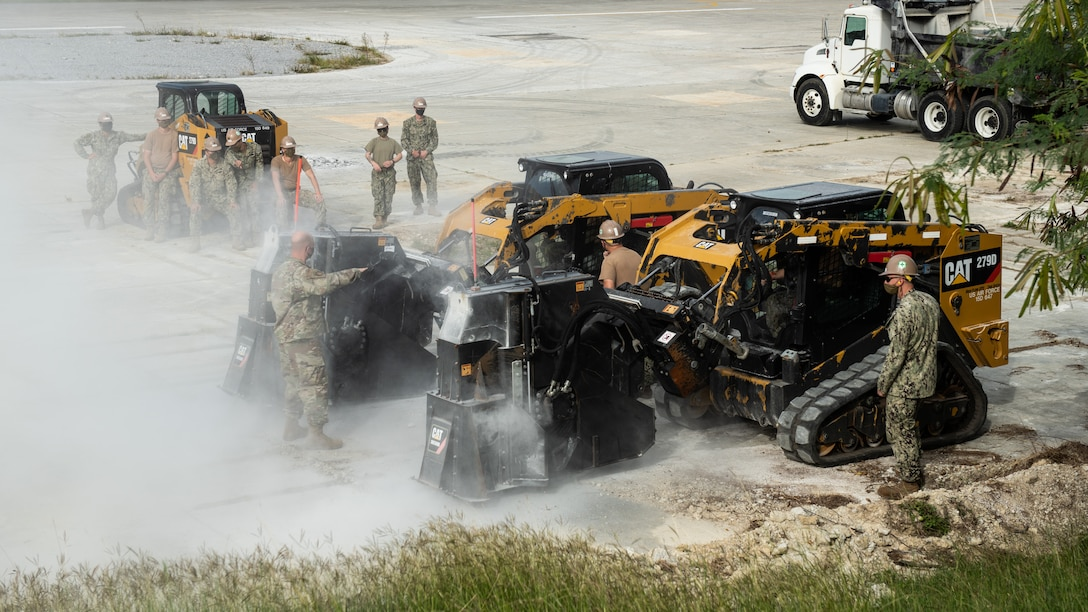 U.S. Air Force 18th Civil Engineer Squadron Airmen and Navy Mobile Construction Battalion 3 Seabees conduct training on compact track loader saws during a rapid airfield damage repair exercise Nov. 18, 2020, at Kadena Air Base, Japan. The joint training exercise enabled the two units to exchange RADR knowledge and integrate training procedures. (U.S. Air Force photo by Staff Sgt. Peter Reft)