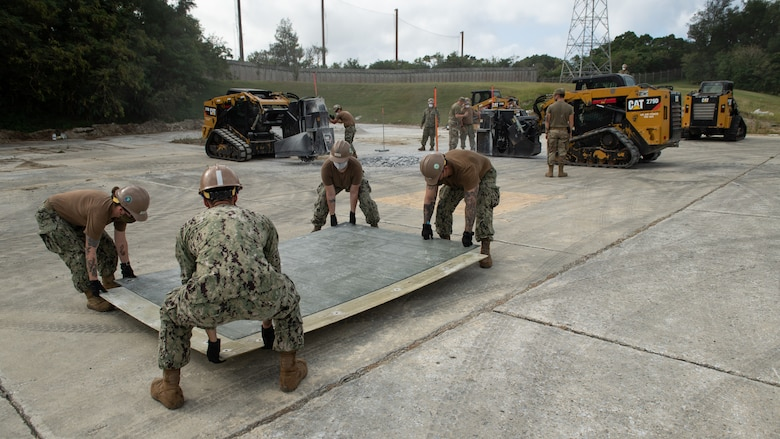 U.S. Air Force 18th Civil Engineer Squadron Airmen and Navy Mobile Construction Battalion 3 Seabees conduct a rapid airfield damage repair exercise Nov. 18, 2020, at Kadena Air Base, Japan. In order to adapt to constantly changing Pacific Theater mission demands, Department of Defense units throughout the U.S. Indo-Pacific Command theater train together in order to innovate training operations and enhance agile force employment capabilities. (U.S. Air Force photo by Staff Sgt. Peter Reft)