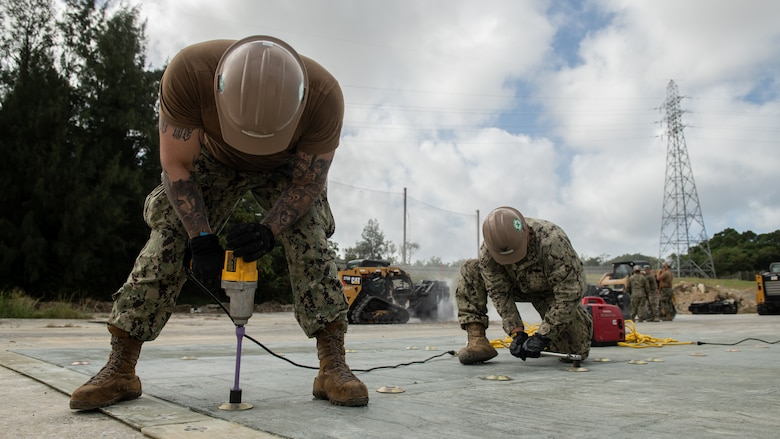 U.S. Navy Mobile Construction Battalion 3 Seabees secure fiberglass panels together during a rapid airfield damage repair exercise Nov. 18, 2020, at Kadena Air Base, Japan. NMCB-3 is deployed across the Indo-Pacific region conducting high-quality construction to support U.S. and partner nations to strengthen partnerships, deter aggression, and enable expeditionary logistics and naval power projection. The battalion stands ready to complete assigned tasking, support Humanitarian Aid/Disaster Relief and Major Combat Operations throughout the area of responsibility. (U.S. Air Force photo by Staff Sgt. Peter Reft)