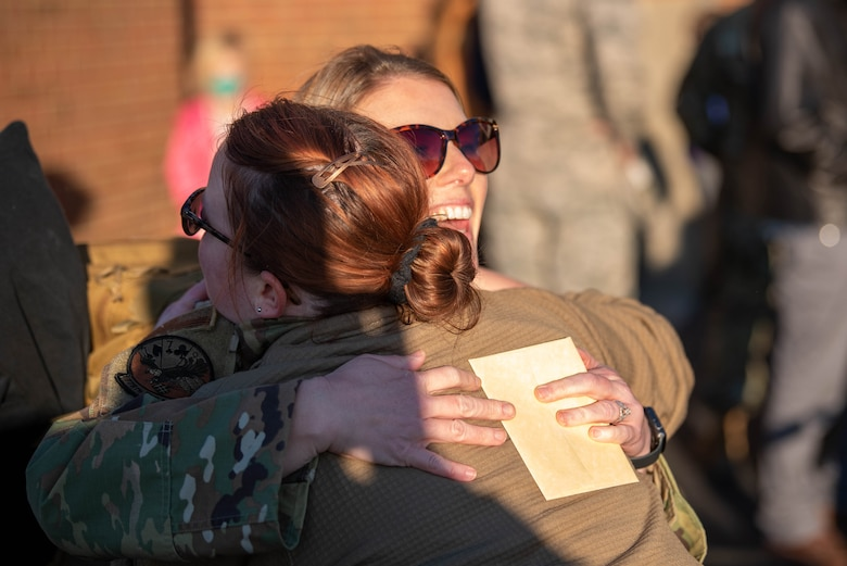 Two Airmen from the 123rd Airlift Wing embrace during a homecoming where more than 90 Airmen from the Kentucky Air National Guard returned to their home base in Louisville, Ky., Nov. 18, 2020, after completing a four-month deployment to the Middle East. The Airmen, who arrived aboard Kentucky Air Guard C-130 Hercules aircraft, operated from an undisclosed air base while flying troops and cargo across the U.S. Central Command Area of Responsibility in support of Operations Inherent Resolve and Freedom's Sentinel. (U.S. Air National Guard photo by Phil Speck)