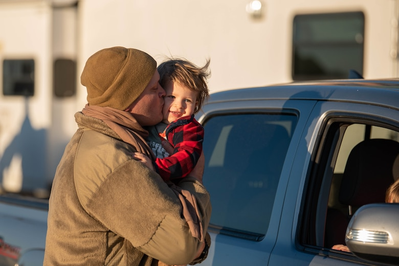Capt. Jason Ketterer, a navigator for the 165th Airlift Squadron, is greeted by his family at the Kentucky Air National Guard base in Louisville, Ky., on Nov. 18, 2020, after completing a four-month deployment to the Middle East in support of Operations Inherent Resolve and Freedom's Sentinel. More than 90 Airmen from the 123rd Airlift Wing arrived aboard Kentucky Air Guard C-130 Hercules aircraft. (U.S. Air National Guard photo by Phil Speck)