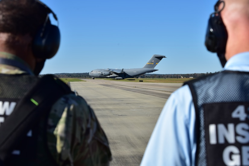 U.S. Air Force Master Sgt. Bradley Moorer, an Inspector General Wing Inspection Team superintendent for the 437th Airlift Wing (right), and Mark Vickers, the 437th AW IG director of inspections (left), monitor Airmen offloading cargo from a C-17 Globemaster III, at McEntire Joint National Guard Base, S.C., Nov. 16, 2020. Palmetto Challenge is a global mobilization exercise held at McEntire Joint National Guard Base, S.C. The exercise is held in order to develop readiness and awareness in a simulated deployed environment for over 100 Airmen from Joint Base Charleston.